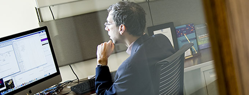 Photo of a man sitting at a desk, wearing a suit, and looking at his computer screen