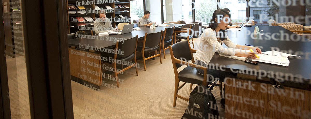Students studying in the library behind a glass wall with white lettering.
