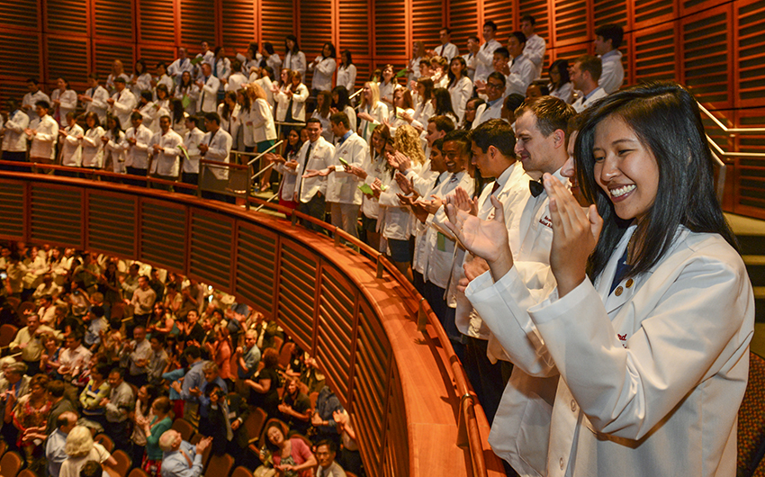 Auditorium full of students wearing white coats and clapping